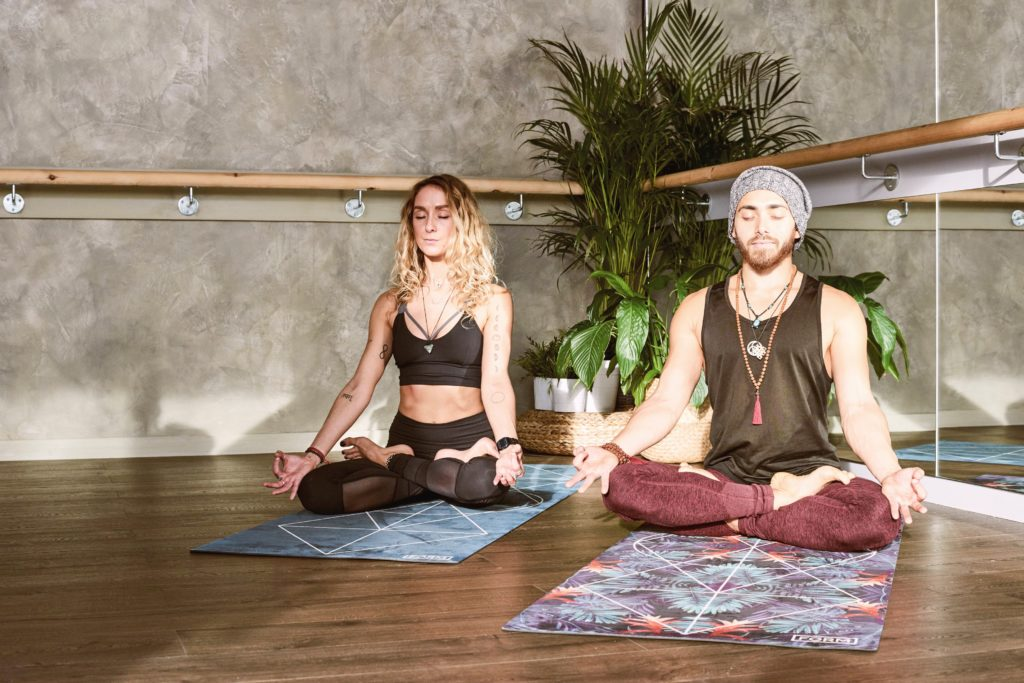 people doing yoga inside an apartment clubhouse